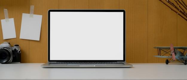 Kantoor aan huis met leeg scherm laptop, camera, decoraties en notitieblok op plank muur