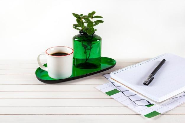 Kantoor aan huis werkruimte mockup met notebook, pen, kopje koffie, tak in glazen vaas