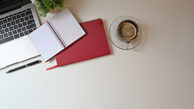 Kantoor bureau bovenaanzicht tafel met laptop, laptop en pen met koffie.