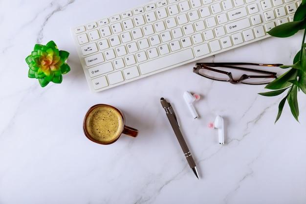 Kantoor bureau tafel met computer levert koptelefoon glazen pen en koffiekopje