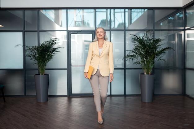 Kantoor gang. volledig portret van een glimlachende elegante vrouw in officiële outfit die een papieren map draagt terwijl ze door de kantoorgang loopt