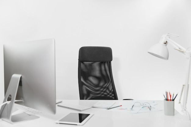 Kantoor licht interieur van werkplek, tafel met moderne computer en modieuze monitor, toetsenbord, muis, documenten, lamp, tablet, potloden, bril en stoel