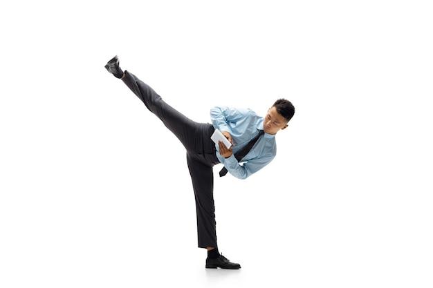 Kantoor man die taekwondo beoefent op witte muur