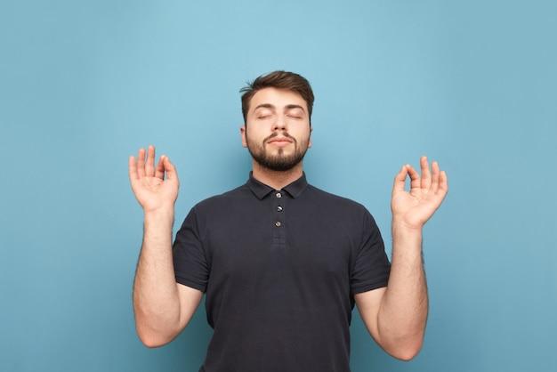 Kantoor man met een baard mediteert met gesloten ogen en opgeheven handen