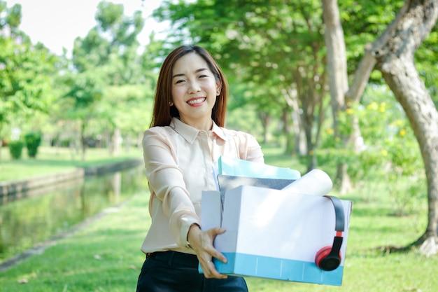 Kantoor meisje houdt een wit papier doos, zet bestanden en muziek koptelefoon happy smile