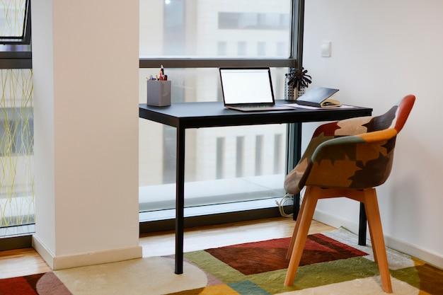 Kantoor met een werktafel met laptop, telefoon en pennen, bij een raam, met een stoel en een kleurig tapijt.
