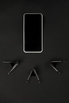 Kantoor. monochroom stijlvolle en trendy compositie in zwart kleuroppervlak. bovenaanzicht, plat gelegd. pure schoonheid van de gebruikelijke dingen in de buurt. copyspace voor advertentie. detailopname. het lege scherm van de smartphone.
