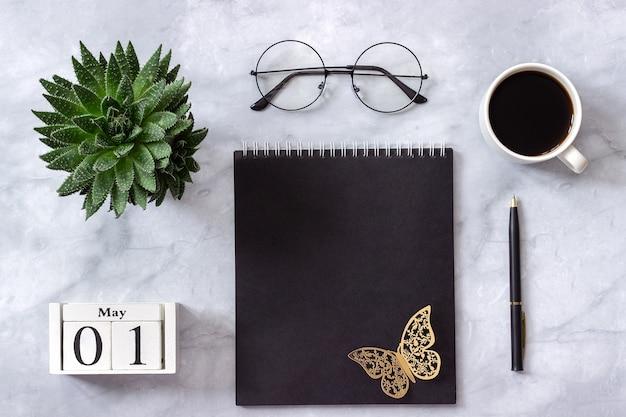 Kantoor- of thuistafelkalender 1 mei. kladblok, koffie, succulent, bril concept stijlvolle werkplek