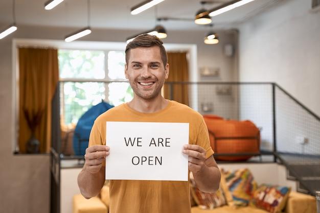 Kantoor openen na afsluiting jonge gelukkige man die papier met tekst laat zien dat we open zijn voor de camera en