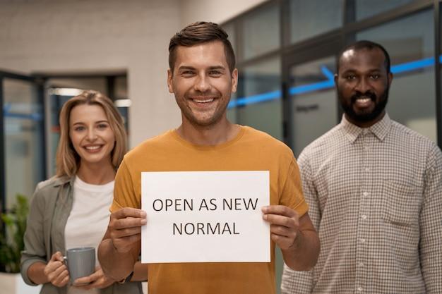 Kantoor opening jonge gelukkige man kantoormedewerker met papier met tekst open als nieuw normaal op camera