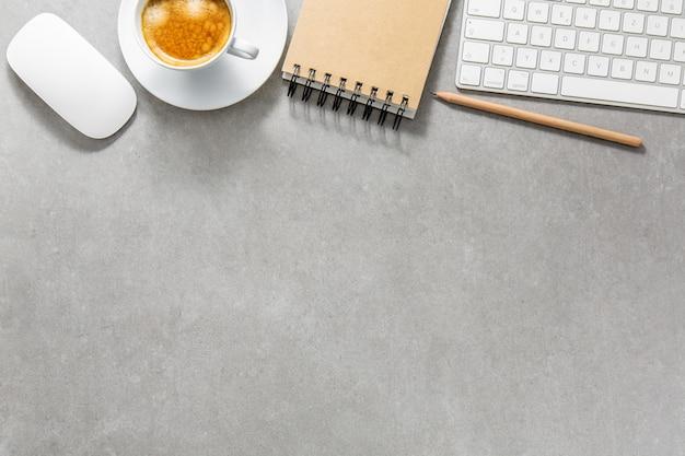 Kantoor tafel met kopje koffie, toetsenbord en kladblok