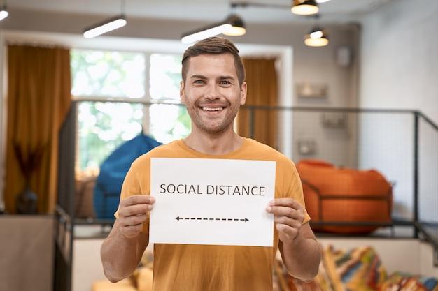 Kantoor veilig heropenen jonge gelukkige man met papier met tekst sociale afstand op camera en