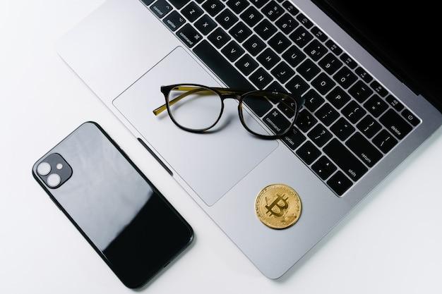 Kantoor werkgebied gouden munten bitcoin laptop mobiele telefoon bril. concept van bitcoin cryptocurrency trading