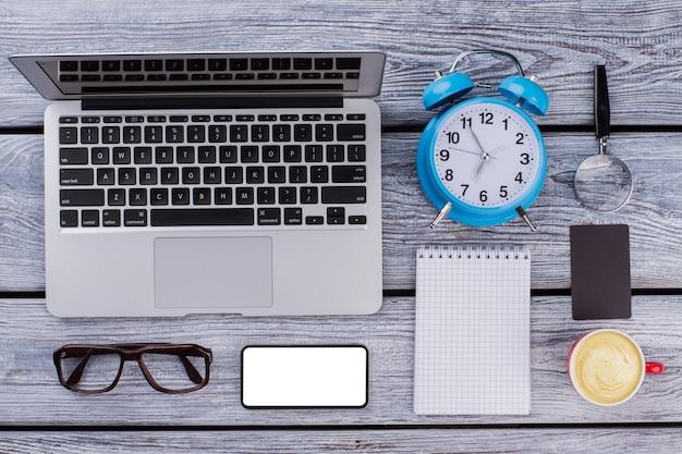 Kantoor werknemer ochtend concept. laptop met smarthphone, kladblok, wekker en kopje koffie op een houten tafel. plat lag bovenaanzicht.