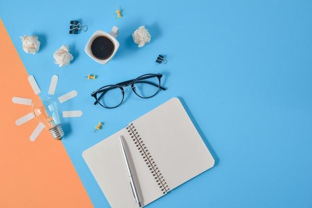 Kantoorartikelen, pen, kladblok, gloeilamp op oranje en blauwe achtergrond.