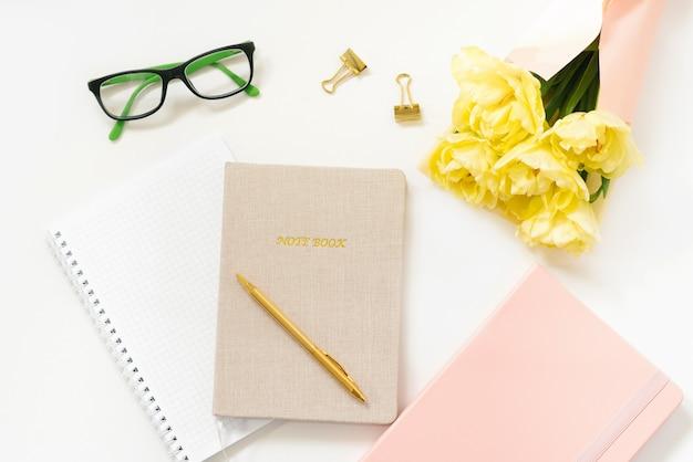Kantoorartikelen voor vrouwenwerk: notitieboekjes, pen, paperclips, gele tulpen en glazen. de stijlvolle platligging van hipster