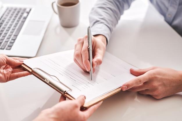 Kantoorbeheerder die medische kaart over zijn gezondheidsstatus aan werknemer geeft ter ondertekening in kantoor
