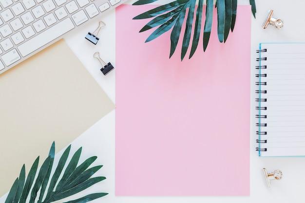 Kantoorbehoeften dichtbij toetsenbord en palmbomen