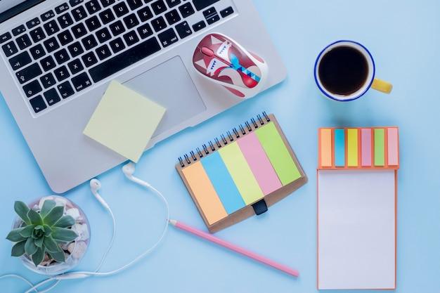 Kantoorbehoeften en koffie dichtbij laptop en oortelefoons