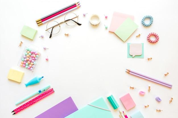 Kantoorbehoeften, meisje dat in pastelkleuren op witte achtergrond wordt geplaatst.