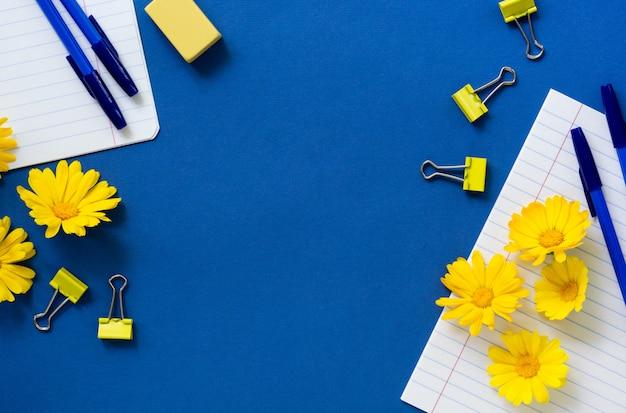 Kantoorbehoeften met goudsbloembloemen op een blauwe achtergrond