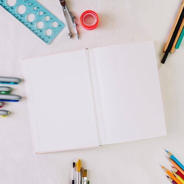 Kantoorbehoeften rond notitieboekje met blanco pagina's