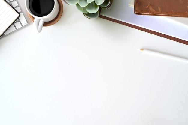 Kantoorbenodigdheden aan het witte bureau en kopieer ruimte