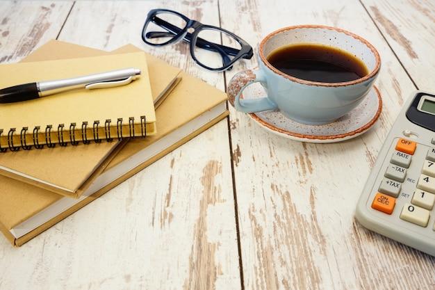 Kantoorbenodigdheden, blocnotes, rekenmachine en een kopje koffie op een retro houten tafel.