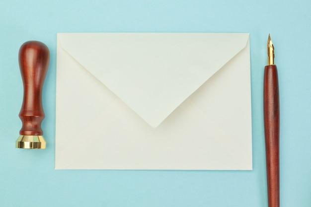Kantoorbenodigdheden en postenvelop op een blauwe muur