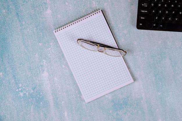 Kantoorbenodigdheden met werkplek op computertoetsenbord zakelijke documenten notitieblok in brillen