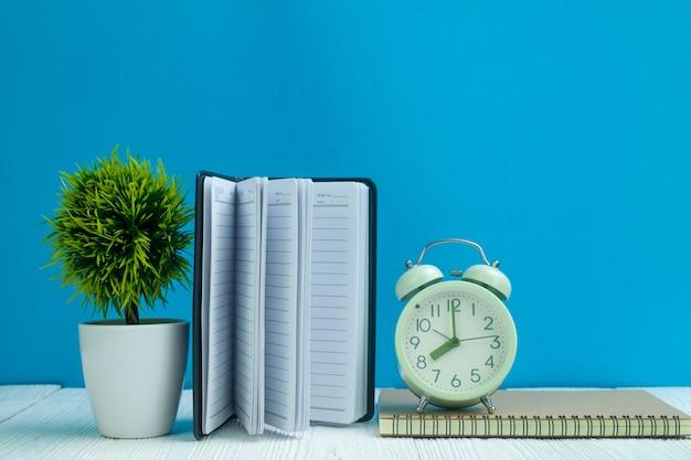 Kantoorbenodigdheden of kantoor werk essentiële gereedschappen items op houten bureau in de werkplaats, laptop, wekker en kleine boom met blauwe muur achtergrond.