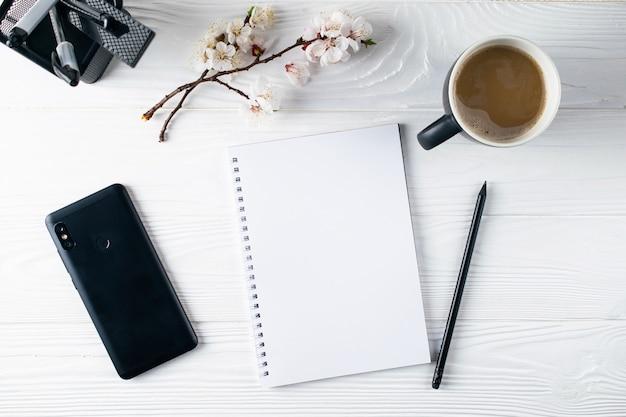 Kantoorbenodigdheden, telefoon, notebook, koffie en pensil, schrijver overhead plat leggen
