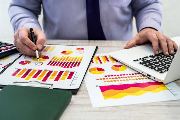 Kantoorberoepszaken, technologie, financiën en concept - jonge zakenman met laptopgrafiekdiagram en documenten op kantoor