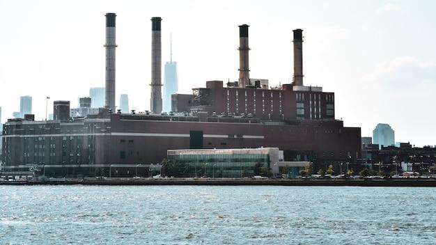 Kantoorgebouwen, appartementen en industriële schoorstenen gebouwen in de skyline bij zonsondergang, vanaf de hudson rivier. verontreiniging en industrieconcept. manhattan, new york city, verenigde staten.