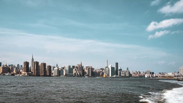 Kantoorgebouwen en appartementen aan de skyline bij zonsondergang, vanaf de hudson rivier. onroerend goed en reisconcept. manhattan, new york city, verenigde staten.