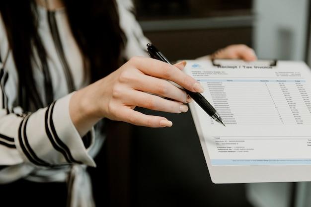 Kantoormedewerker die het ontvangstbewijs en de belastingfactuur aan de klant toont