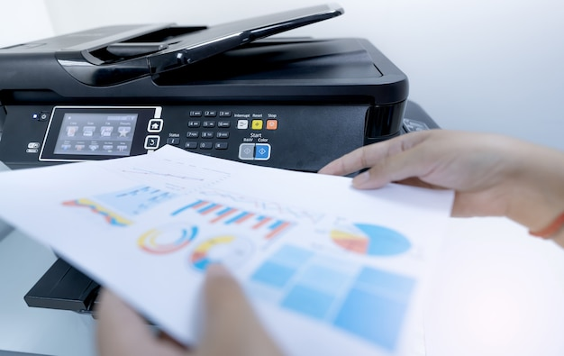 Kantoormedewerker drukt papier af op multifunctionele laserprinter kopieer print scan- en faxapparaat