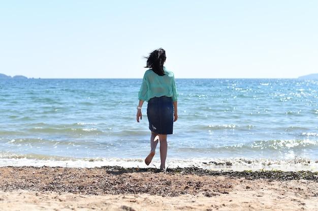 Kantoormedewerker loopt naar de zee na het concept van werkvrijheid