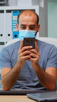 Kantoormedewerker met beschermend masker met behulp van telefoon typen zittend op modern kantoor tijdens coronavirus. freelancer aan het werk op een nieuwe, normale werkplek, pratend pratend schrijvend met behulp van mobiele internettechnologie