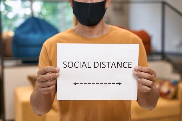 Kantoormedewerker met een zwart beschermend masker met papier met sociale tekst