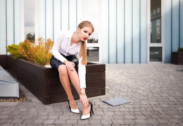 Kantoormedewerker voelt pijn in de benen door het dragen van hakken. moe werknemer lijdt aan gewrichtspijn