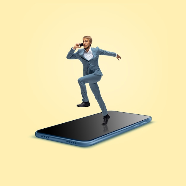 Kantoormedewerker zakenman in pak draait op het oppervlak van gigantische smartphones scherm