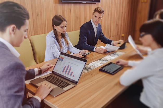 Kantoormedewerkers houden een vergadering aan een bureau voor laptops, tablets en kranten, een grote tv op een houten muur