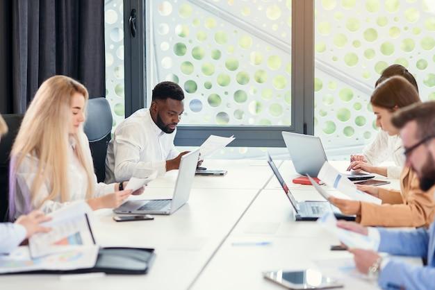 Kantoormensen gaan op in hun werk aan de vergadertafel