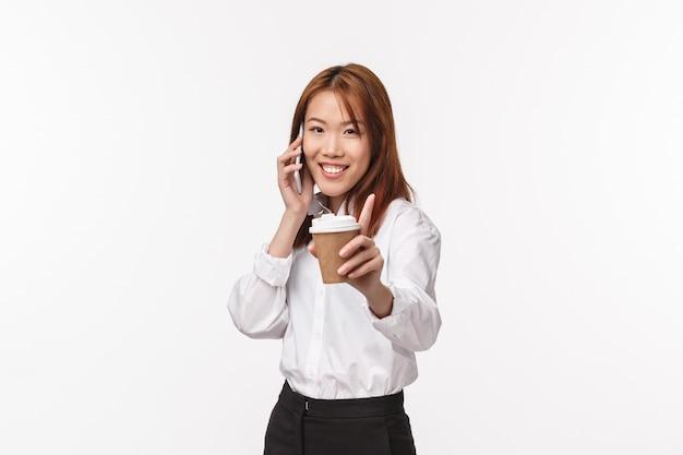 Kantoorwerk, mensen en levensstijl concept. vrolijke dwaze jonge aziatische vrouw die u haar kopje koffie suggereert tijdens het praten over de telefoon, camera blij glimlachen, gesprek hebben,