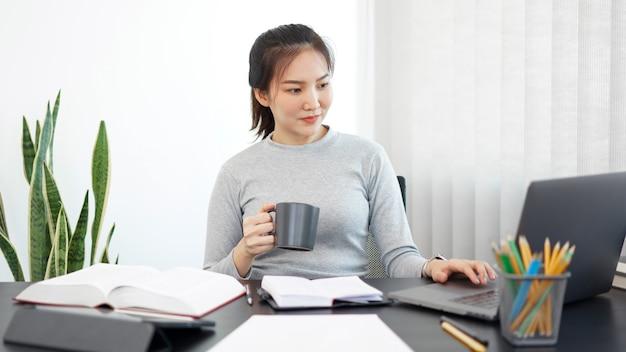 Kantoorwerkconcept een vrouwelijke secretaresse die een kopje koffie vasthoudt en ontspannen haar werk doet.