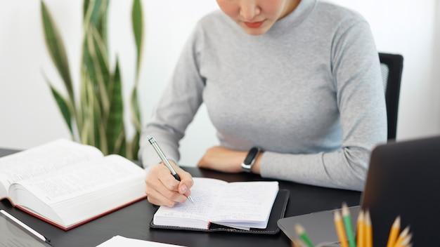 Kantoorwerkconcept een vrouwelijke secretaresse die gretig wat informatie in een notitieboekje schrijft.
