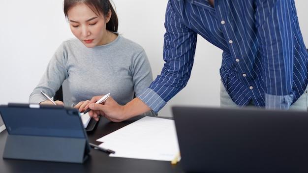 Kantoorwerkconcept twee zakenpartners die naar een tabletscherm kijken en een gesprek voeren over een zakelijk onderwerp.