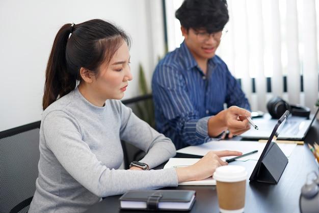 Kantoorwerkconcept twee zakenpartners die naar een tabletscherm kijken en een gesprek voeren