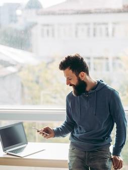 Kantoorwerkplek man staat op het punt een zakelijk gesprek te voeren voor het raam
